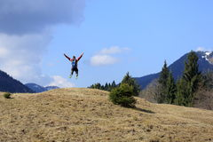 Jumping up in front of the mountains Royalty Free Stock Photography