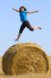Jumping Up On Straw Roll Stock Photography