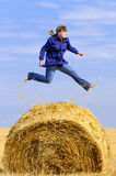 Jumping up on straw roll Royalty Free Stock Image