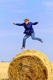 Jumping up on straw roll Stock Images
