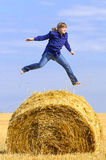 Jumping up on straw roll Royalty Free Stock Photos