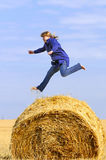 Jumping up on straw roll Stock Photo