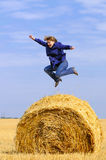 Jumping up on straw roll Stock Photos
