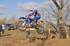 Jumping upwards rider up on a motorcycle MX Stock Image