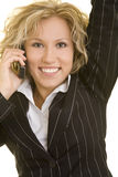 Jumping while using the phone. Blonde business woman making a phone call and jumping happily in the air royalty free stock images