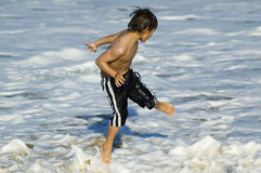Jumping the wave #3. Young boy jumping over the waves breaking on the beach Royalty Free Stock Photos