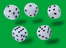 Jumping white dices thrown in a craps game, yatsy or any kind of dice game against a green background. Stock image royalty free stock image