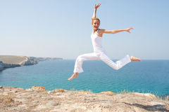 Jumping woman. In white cloth against the sea Royalty Free Stock Photo