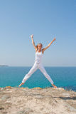 Jumping woman. In white cloth against the sea Stock Image