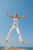 Jumping woman. In white cloth against the sea Stock Photo