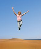 Jumping woman. A happy blond woman is jumping in the sky above a sand beach Royalty Free Stock Image
