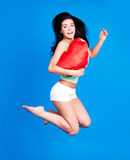 Jumping woman. Happy jumping young  woman holding a heart-shaped pillow,  against white background Stock Photography