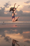 Jumping woman. Young asian woman jumping in the air on beach at sunset Royalty Free Stock Photo