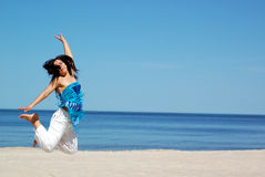 Jumping woman. Attractive woman jumping on the sunny beach Royalty Free Stock Image