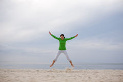 Jumping woman. Active woman jumping on the beach Royalty Free Stock Photography