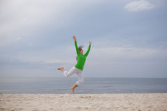 Jumping woman. Active woman jumping on the beach Stock Photos