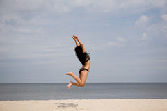 Jumping woman. Active woman jumping on the beach Royalty Free Stock Photos