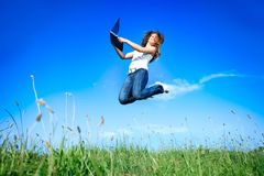 Jumping woman with laptop Stock Photos