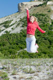 Jumping woman at the mountains Stock Photo