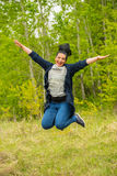 Jumping woman in nature. Laughing jumping woman in nature with forest in background Stock Photos
