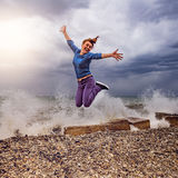 Jumping woman on the sea coast. Jumping woman on the sea coast at the cloudy day time Stock Photo