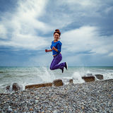 Jumping woman on the sea coast. Jumping woman on the sea coast at the cloudy day time Royalty Free Stock Photos