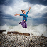 Jumping woman on the sea coast. Jumping woman on the sea coast at cloudy day time Royalty Free Stock Images