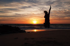 Jumping woman silhouette at the sunset in the beach. Vieux Boucau, France Stock Photo
