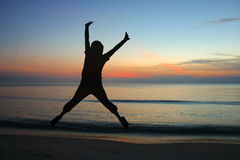 Jumping woman silhouettes with sunrise. Jumping woman silhouettes with sunrise background Stock Photo