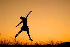 Jumping woman and sunset silhouett Royalty Free Stock Images