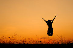 Jumping woman and sunset silhouette Royalty Free Stock Photography
