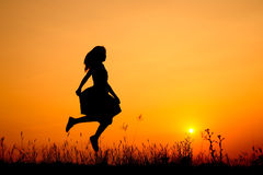 Jumping woman and sunset silhouette Royalty Free Stock Photo