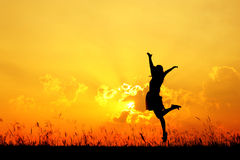 Jumping woman and sunset silhouette Stock Photography