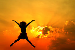 Jumping woman and sunset silhouette Stock Image