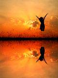 Jumping woman and sunset silhouette,water reflect Royalty Free Stock Images