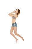 Jumping woman wearing shorts and bra. Royalty Free Stock Photography