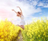 Jumping Woman in yellow field royalty free stock image