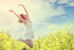 Jumping Woman in yellow field. Toned image royalty free stock photos