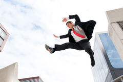 Jumping young business man. Jumping young buiness man in front of buildings Stock Photography
