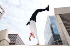 Jumping young business man. In front of buildings Royalty Free Stock Photos