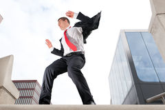 Jumping young business man. Jumping young buiness man in front of buildings Stock Image