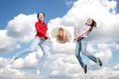 Jumping young girls with paper money mother Royalty Free Stock Image