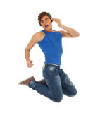 Jumping young handsome man in headphones Stock Photos