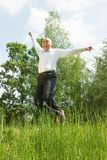 Jumping young smiling men against summer meadow Stock Photo