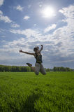 Jumping young woman in the field Stock Photo