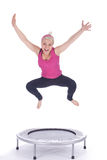 Jumping young woman on the trampoline Stock Images