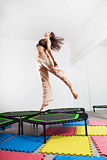 Jumping young woman on a trampoline Stock Image