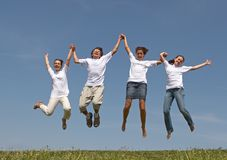 Jumps 2. Three nice girls and young the man jump on a green grass on a background of the blue sky Stock Photography
