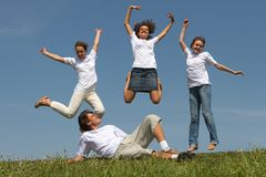 Jumps. Three nice girls jump on a green grass on a background of the blue sky, and young the man lays before them and looks at them from below Stock Photography
