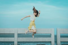 Jumpshot Photography of Woman in White and Yellow Dress Near Body of Water Stock Photos
